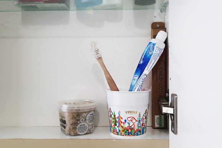 tivoli-cup-holding-toothpaste-and-brush-in-bathroom-cabinet