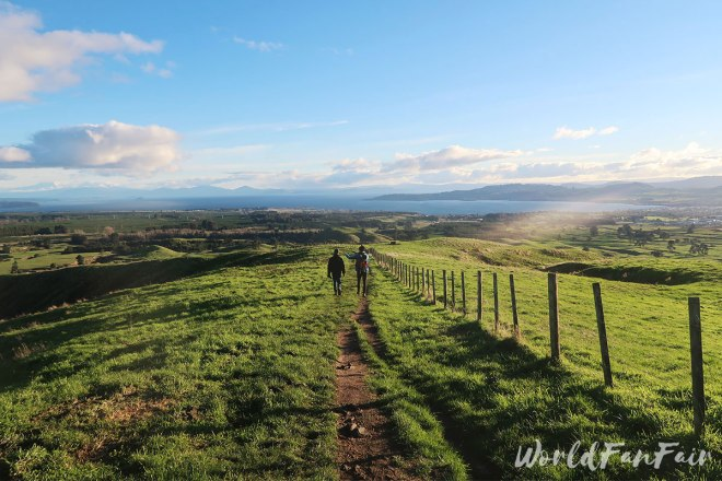 Friends descend the paddocks toward Lake Taupo in the sunset